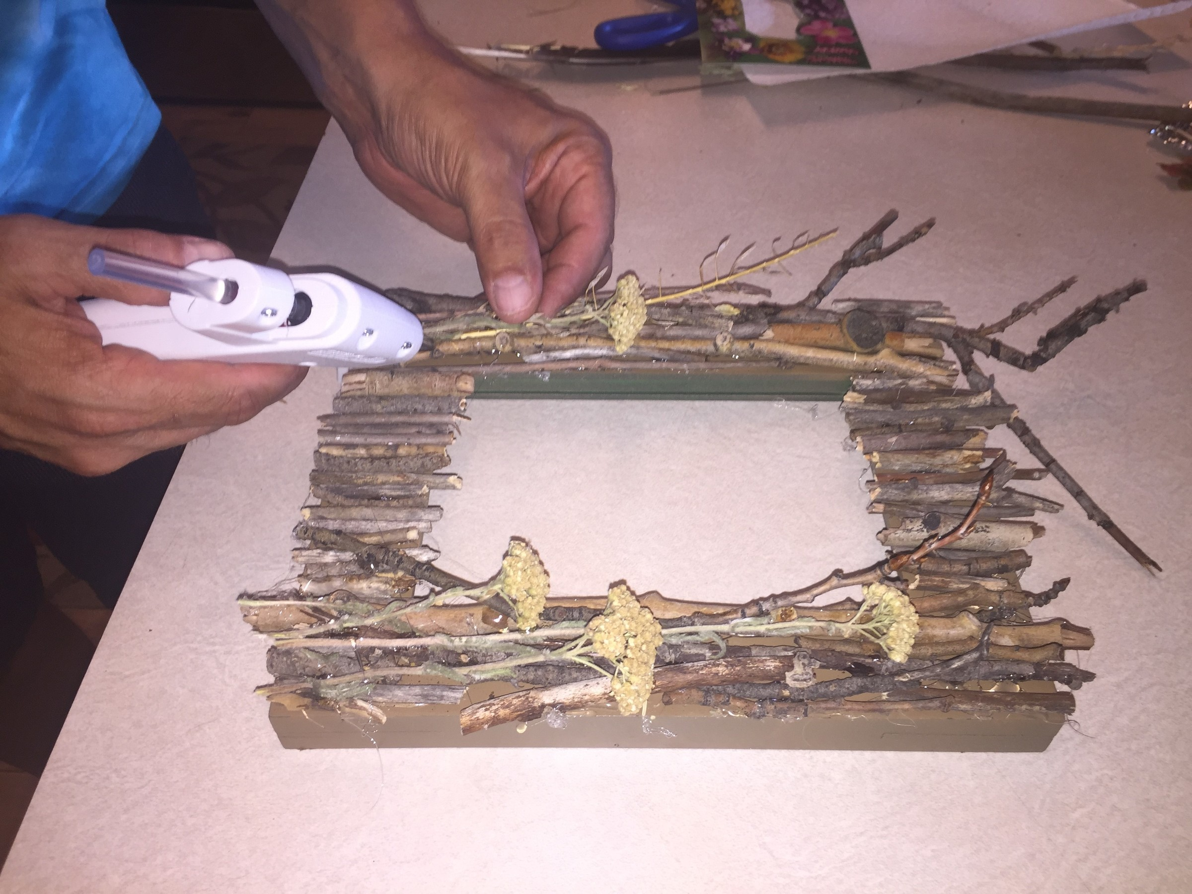 Tim hot glues twigs and flowers to a painted picture frame.