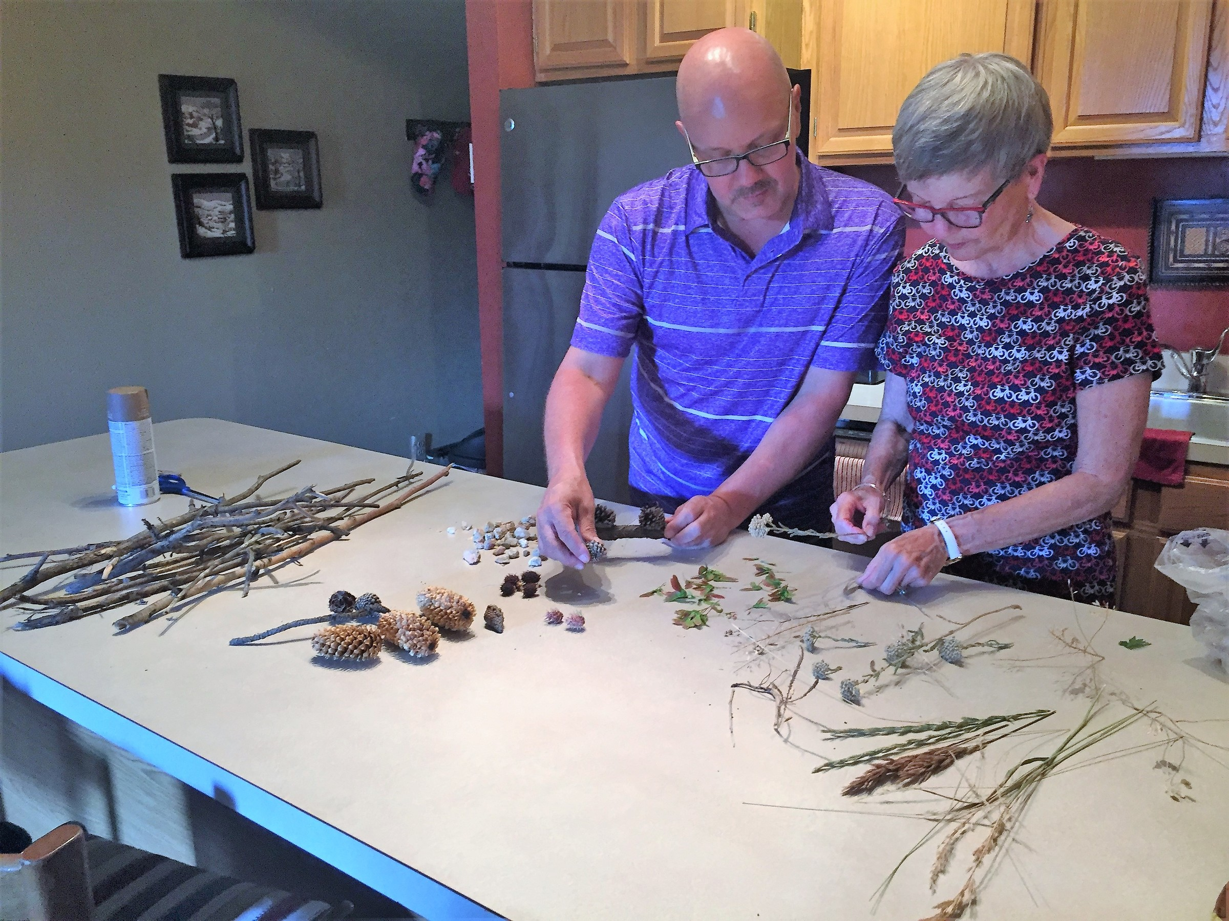 Tim and his Mother sort through natural items used to decorate their frames