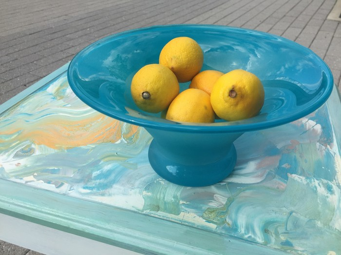Tim displays a completed photo frame tray and painted sea glass bowl full of lemons