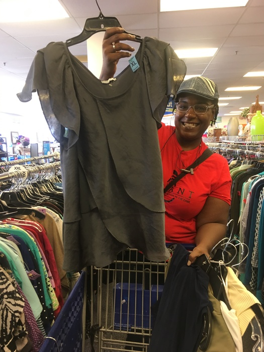 Shopper shows off blouse found at Waldorf Goodwill Meetup