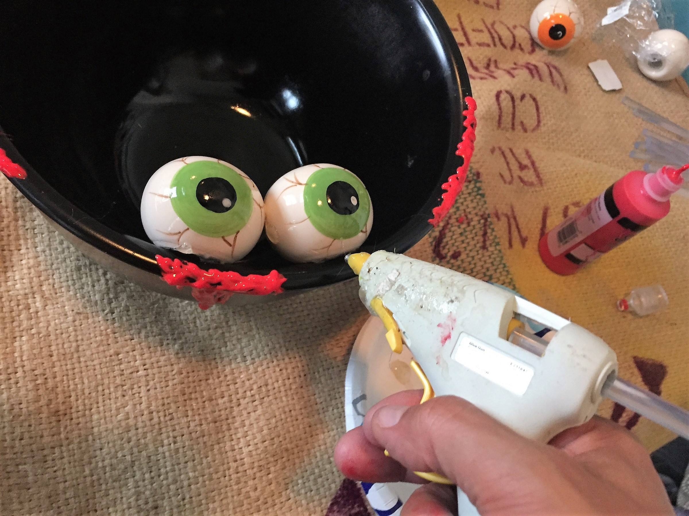 Tim secures spooky eyeballs to painted bowl with hot glue gun.