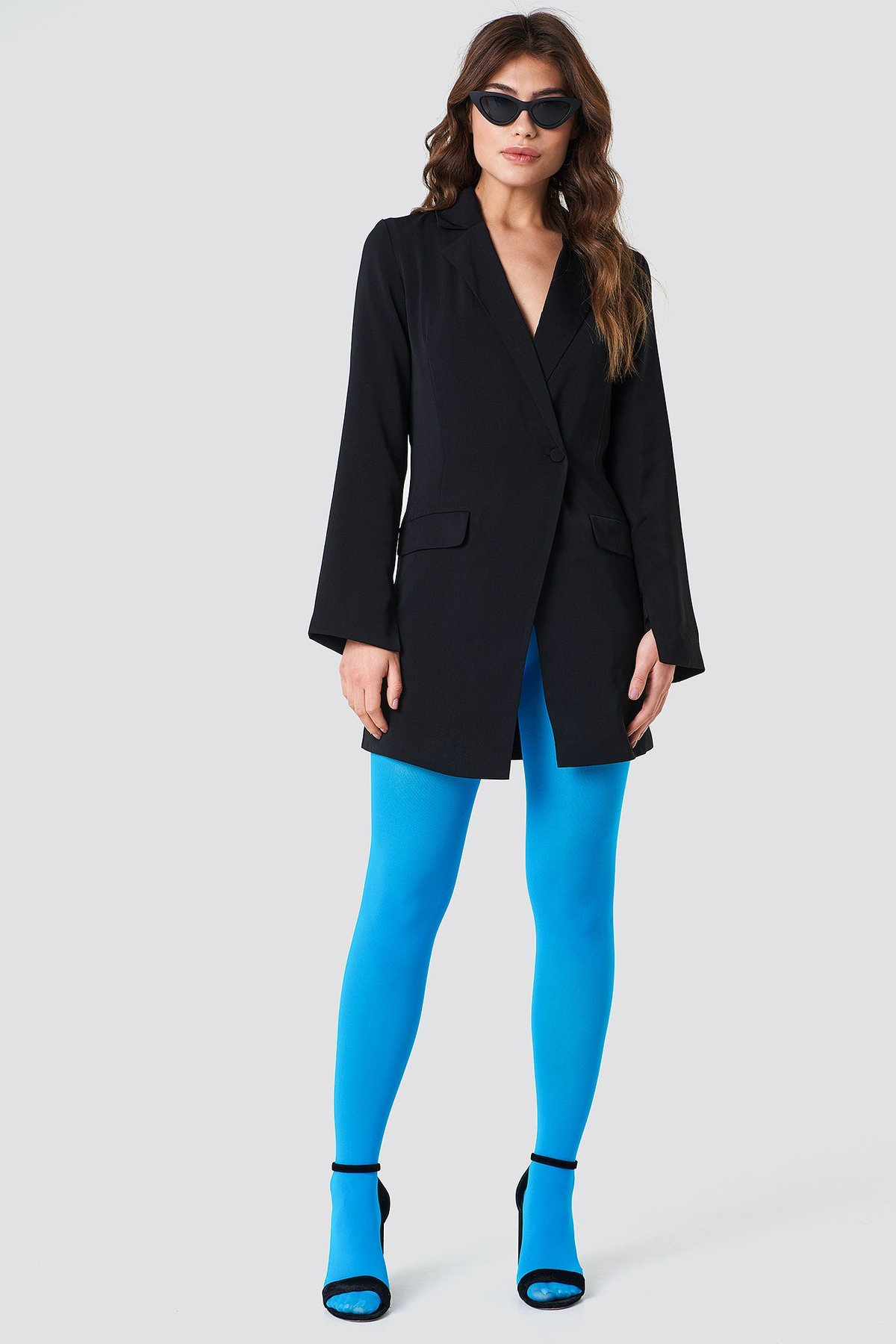 Model wears neon blue tights with a black blazer dress