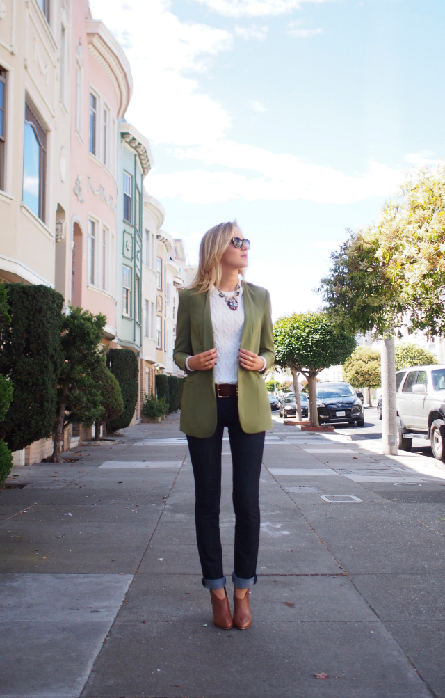 Model wears green blazer, jeans, and crisp white shirt