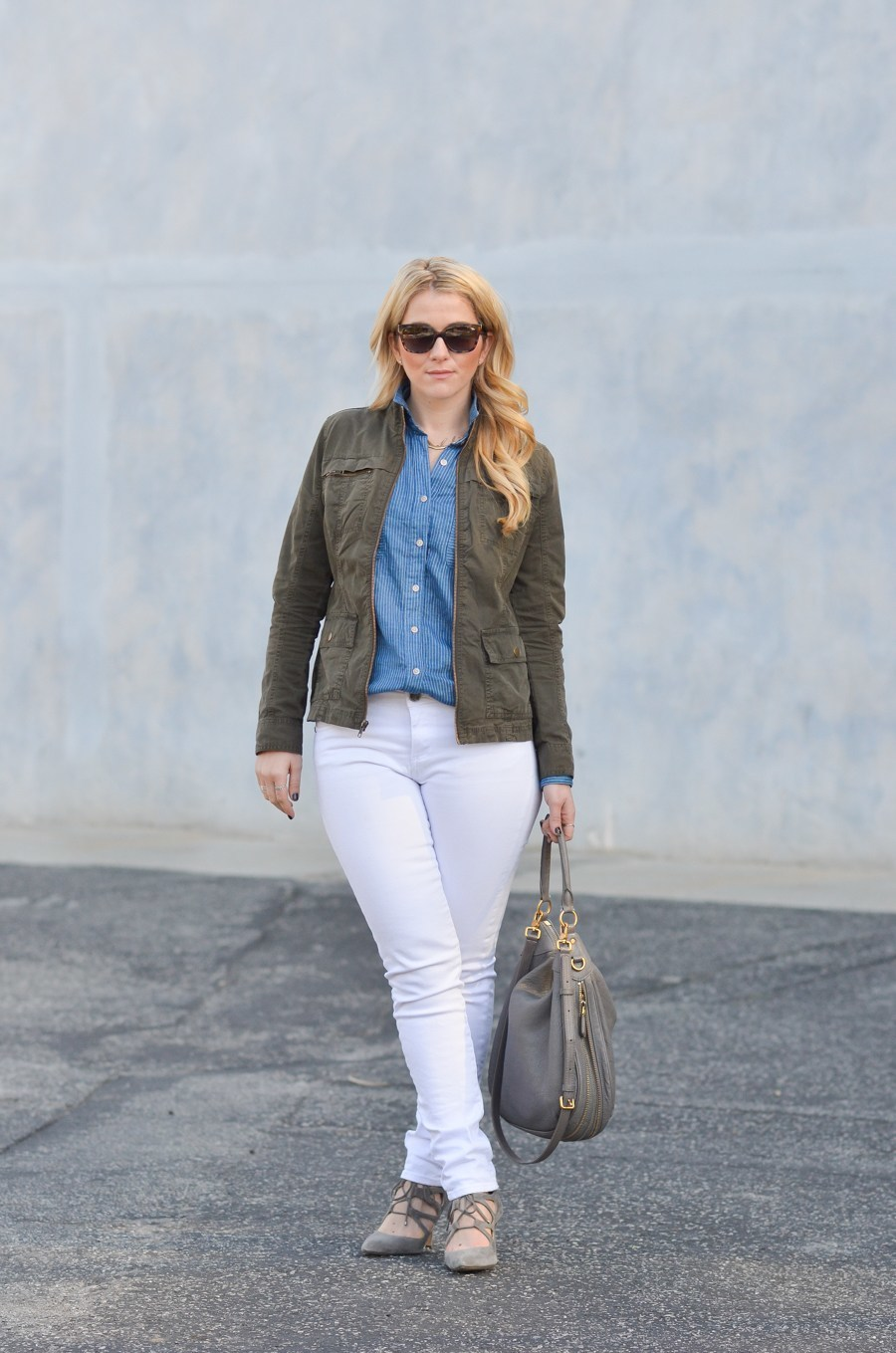 woman wears green utility jacket and white pants