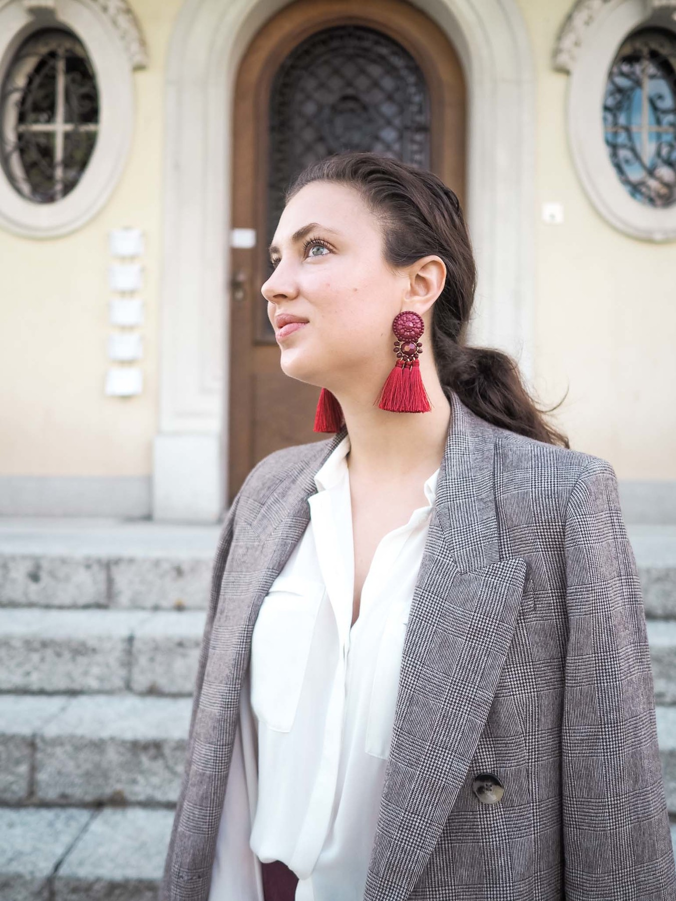 Model wears a grey blazer and trendy tassel earrings in the color oxblood