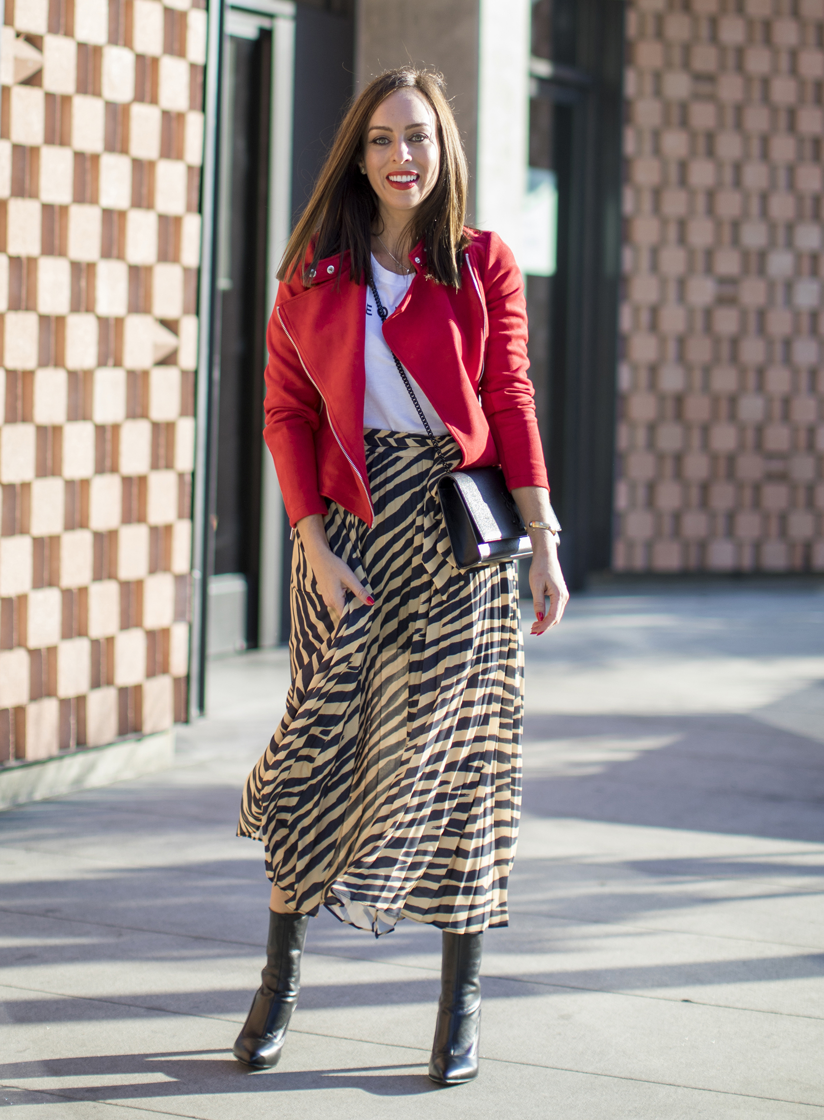 woman pairs a flowy zebra print skirt with boots and a red jacket