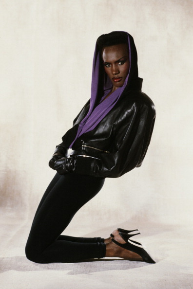 Grace Jones poses in black leggings, a head scarf, and leather jacket.