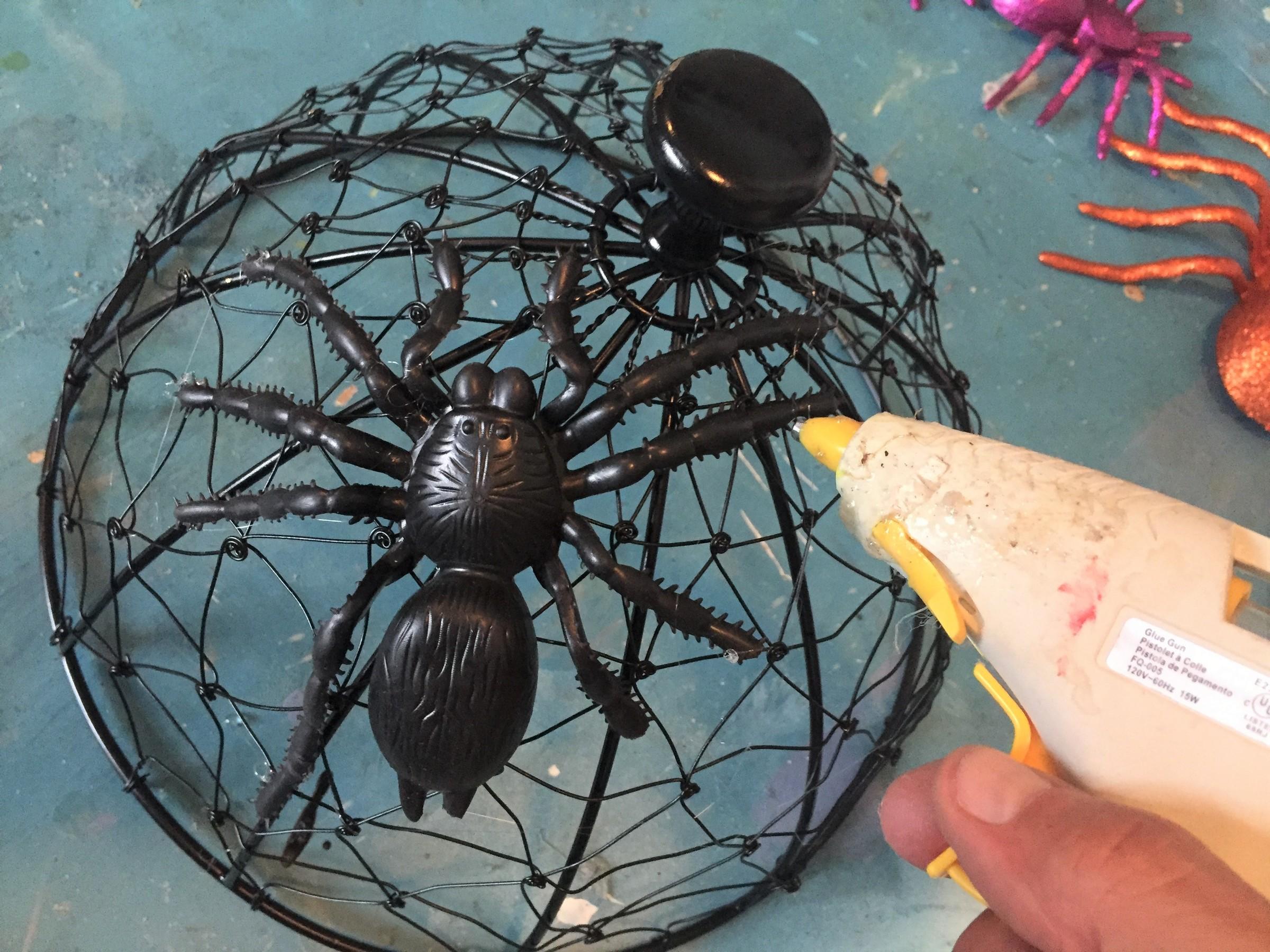 Tim glues a fake spider onto the spray-painted server