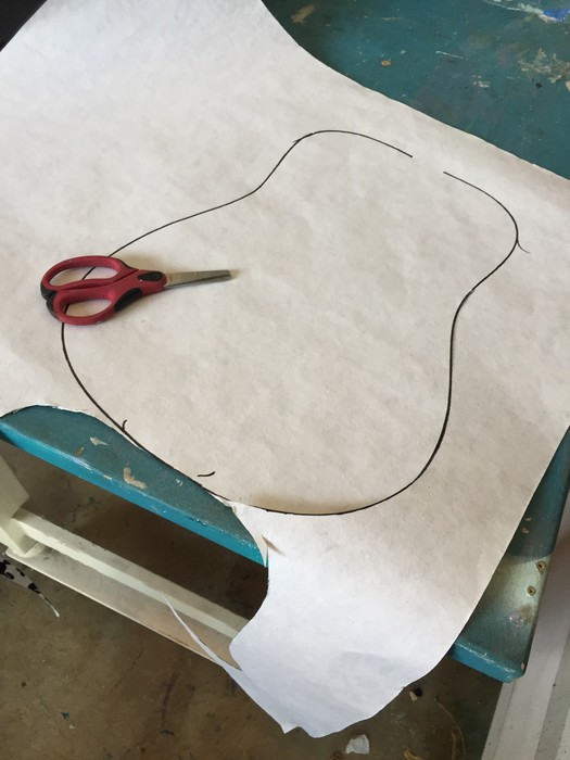 Tim traces the shape of the guitar on contact paper